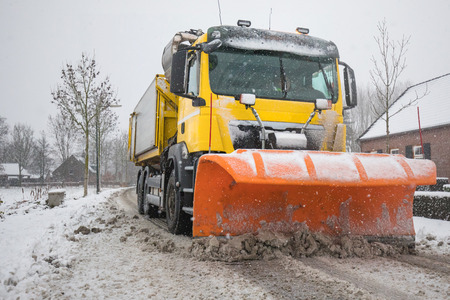 Truck with Snowplow removes snow off icy road in winter