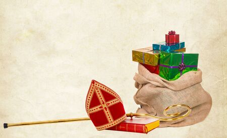Mitre or miter, sack, gifts and staff of saint nicholas. On a Vintage paper background. Stockfoto