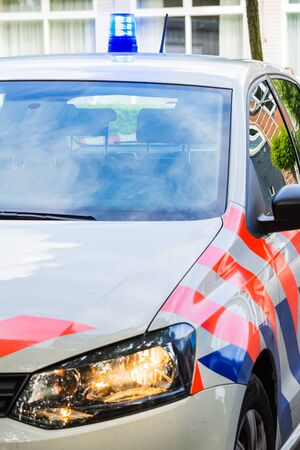 dutch police car with siren and headlights on. Front view