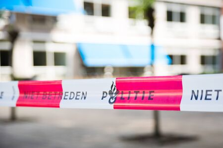 Dutch police line. Do not cross. Red plastic tape on a crime scene.