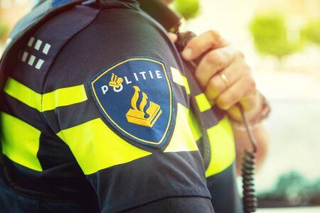 Detail des niederländischen Polizeibeamten, mit tragbarem oder Radio. Fokus auf Abzeichen Standard-Bild