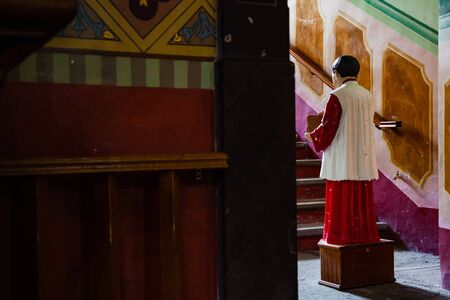 altar boy collecting money with donation box for catholic church. conceptual image