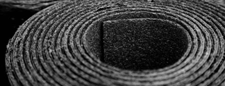 Closeup of Roll of new black roofing felt or bitumen. Shallow depth off field