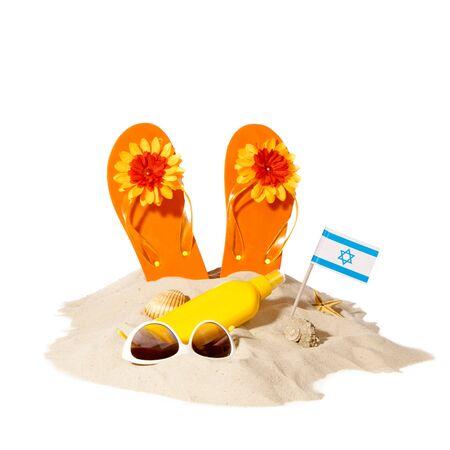 Beach items with flip flops and flag israel on a sunny pile of sand. Beach concept 스톡 콘텐츠