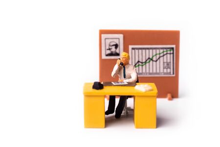 Miniature people businessman holding telephone sitting behind his work desk with graph on the background. Macro shot of Tiny people business concept.