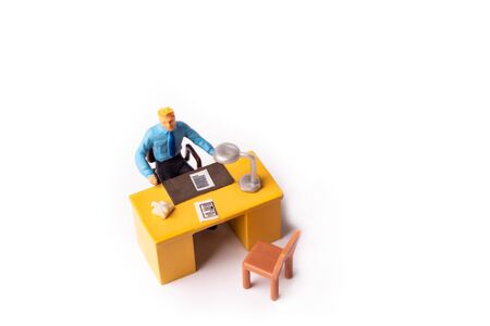 Miniature people businessman sitting behind his work desk. Macro shot from above of Tiny people business concept.