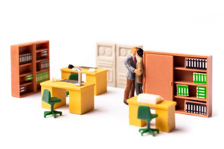Miniature man Gay Couple, Two Tiny People Men Kissing Each other at the office, Concept of Homosexual Relationship. Shallow Depth of Field