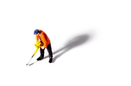 Little People Builder worker with pneumatic hammer drill equipment on white background. Shot from above with shadow