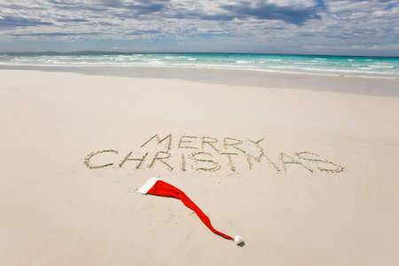 australia beach: Merry Christmas written on a tropical beach with a santa hat on the sand below