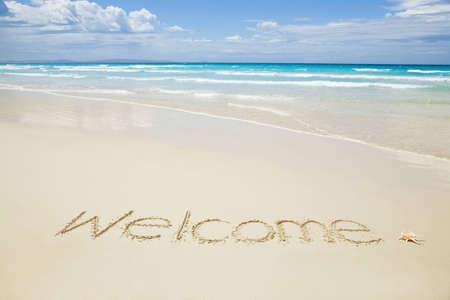 sand writing: Welcome written on a tropical beach
