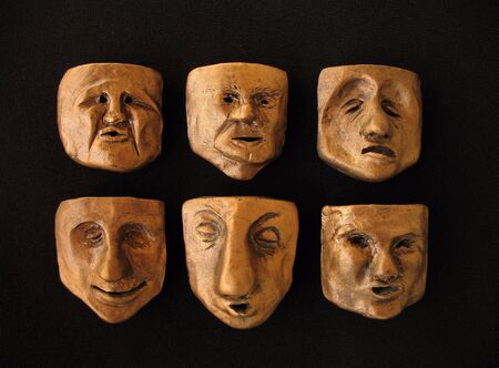 Six bronzed clay faces