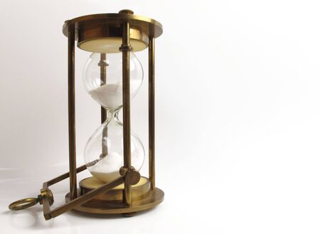 Old brass hourglass on a white background with space for copy                                Stock Photo
