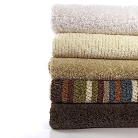 Folded stack of  5 fresh bath towels with solids and one stripe on white