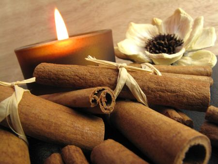 votive candle: Bundled cinnamon sticks with  votive candle and dried flower                                Stock Photo