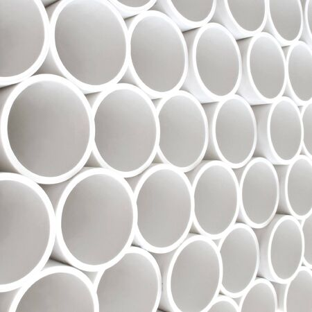 Interesting perspective of new white PVC pipes stacked on a pllet                                Stock Photo