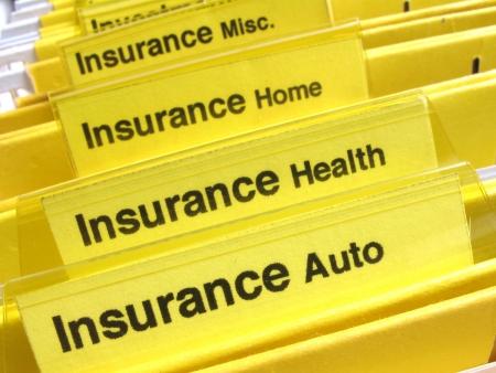 Gele mappen tonen verschillende types van verzekerings papieren                                Stockfoto - 7438853
