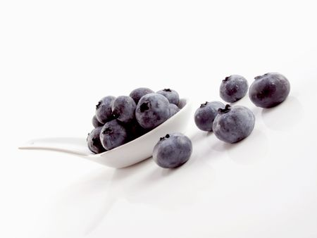 tilted view: Tilted view of a white spoon filled with fresh chilled blueberries