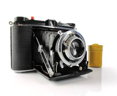 vintage photo: Nice vintage camera with a yellow film canister on white                                Stock Photo
