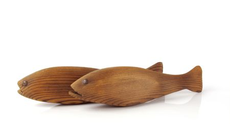 Two hand carved wooden fish swimming across a white background                                photo