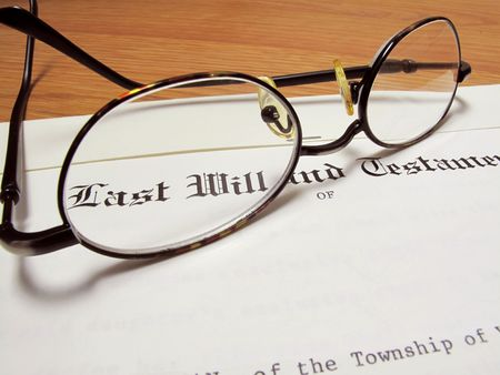 Actual last will and testament with eyeglasses on wooden desk                                photo