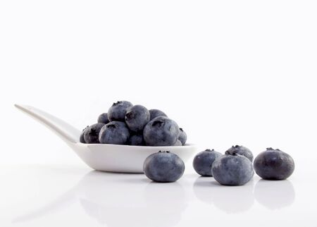 Fresh, chilled ripe blueberries spill from a white spoon                                Zdjęcie Seryjne