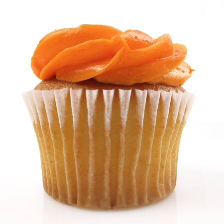 Single yellow cupcake with orange icing on white