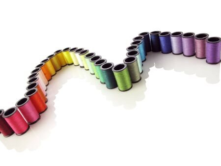 Very colorful rainbow of sewing thread forms a nice curve on white                                Stock Photo
