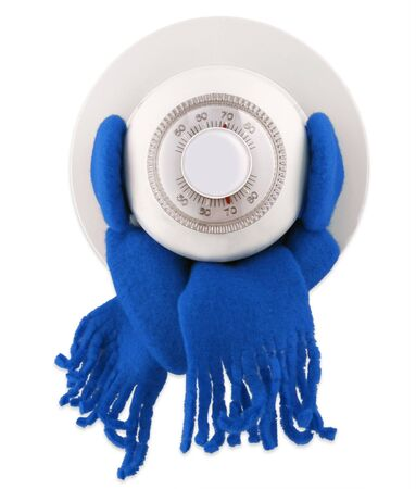 Chilly thermostat with earmuffs and a scarf to keep toasty warm                                Stock Photo