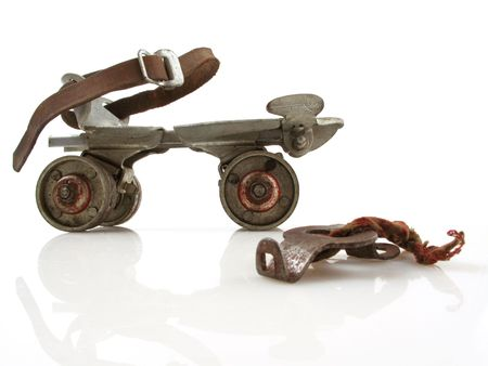 Old clamp-on roller skate with adjustment key on white
