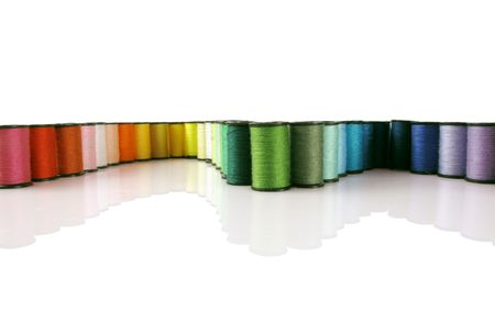 Rainbow of colorful thread spools on a white reflective background                                Stock Photo