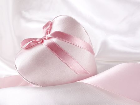 Luxurious and delicate pink satin heart on white satin background