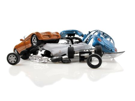 Multi-car pile up involving 3 differnt toy cars on white