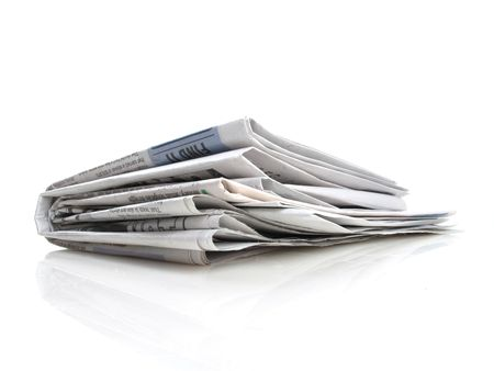 Stack of folded newspapers on a white background                                Stock Photo