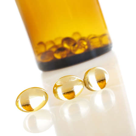 Macro view of vitamin D capsules on white with bottle in background