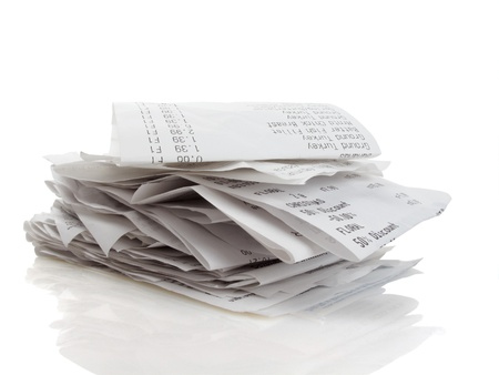 Stack of receipts piled high on white background                                photo