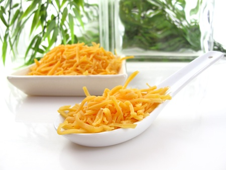 Freshly grated cheddar cheese presented in a white tasting spoon                                Standard-Bild
