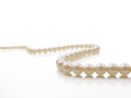 Beautiful creamy pearl necklace on a white reflective surface
