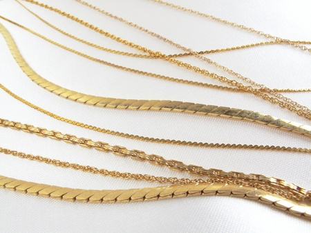 Gold necklace chains in a variety of beautifully crafted links on white satin                                Stock Photo