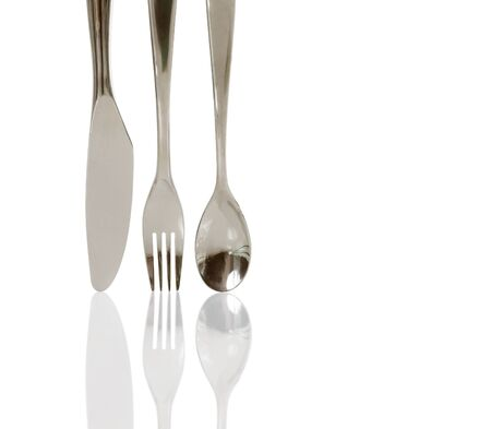 Close-up of a knife, fork and a spoon refected on white