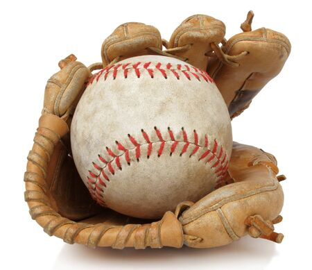 Isolated close up of a worn softball and vintage baseball glove