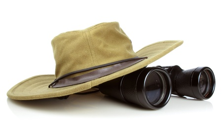 Old canvas hikers hat with a pair of vintage binoculars on white                                Stock Photo