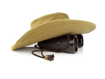 Old hikers hat with a pair of black binoculars on a white background Stock Photo