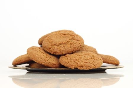 Small gold plate of little ginger snaps on white photo