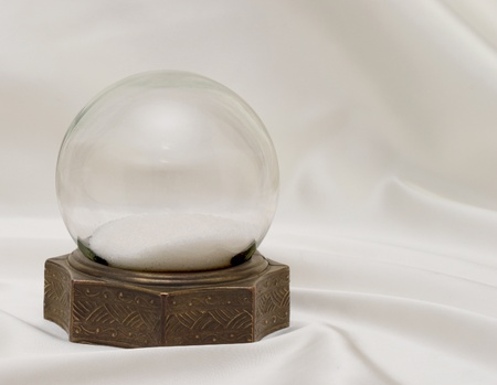Very old antique snow globe with brass base on white satin