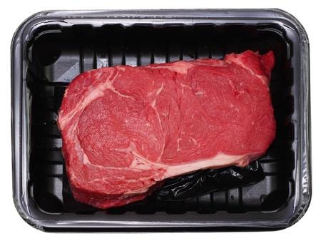 steak cru: Frais bifteck de Delmonico ou nervure isol� sur blanc dans le paquet noir Banque d'images