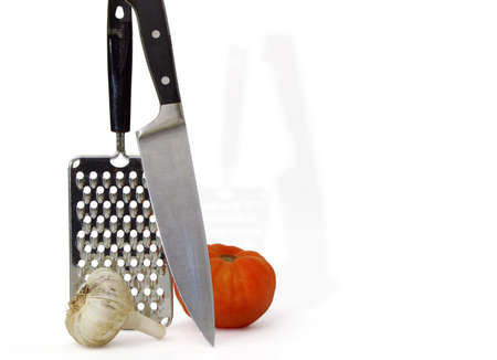grate: Chefs tool with garlic and tomato on white Stock Photo