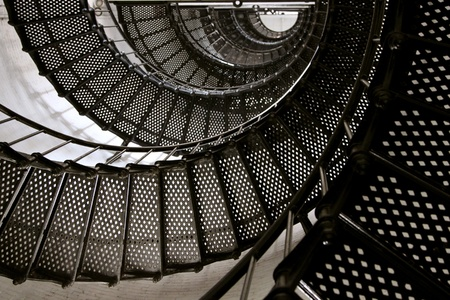 stair well: Black metal spiral staircase goes up inside the lighthouse Stock Photo