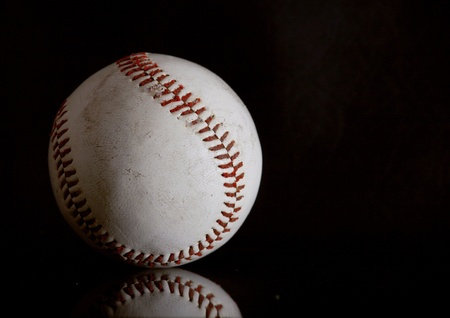 Well used baseball on a black reflective surface Stock Photo