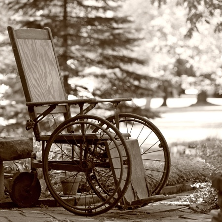 Old wooden wheelchair sits waiting in the garden photo
