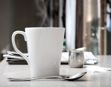 creamer: Mug of hot coffee or tea with stainless creamer and morning newspaper on counter  Intentionally desaturated for effect